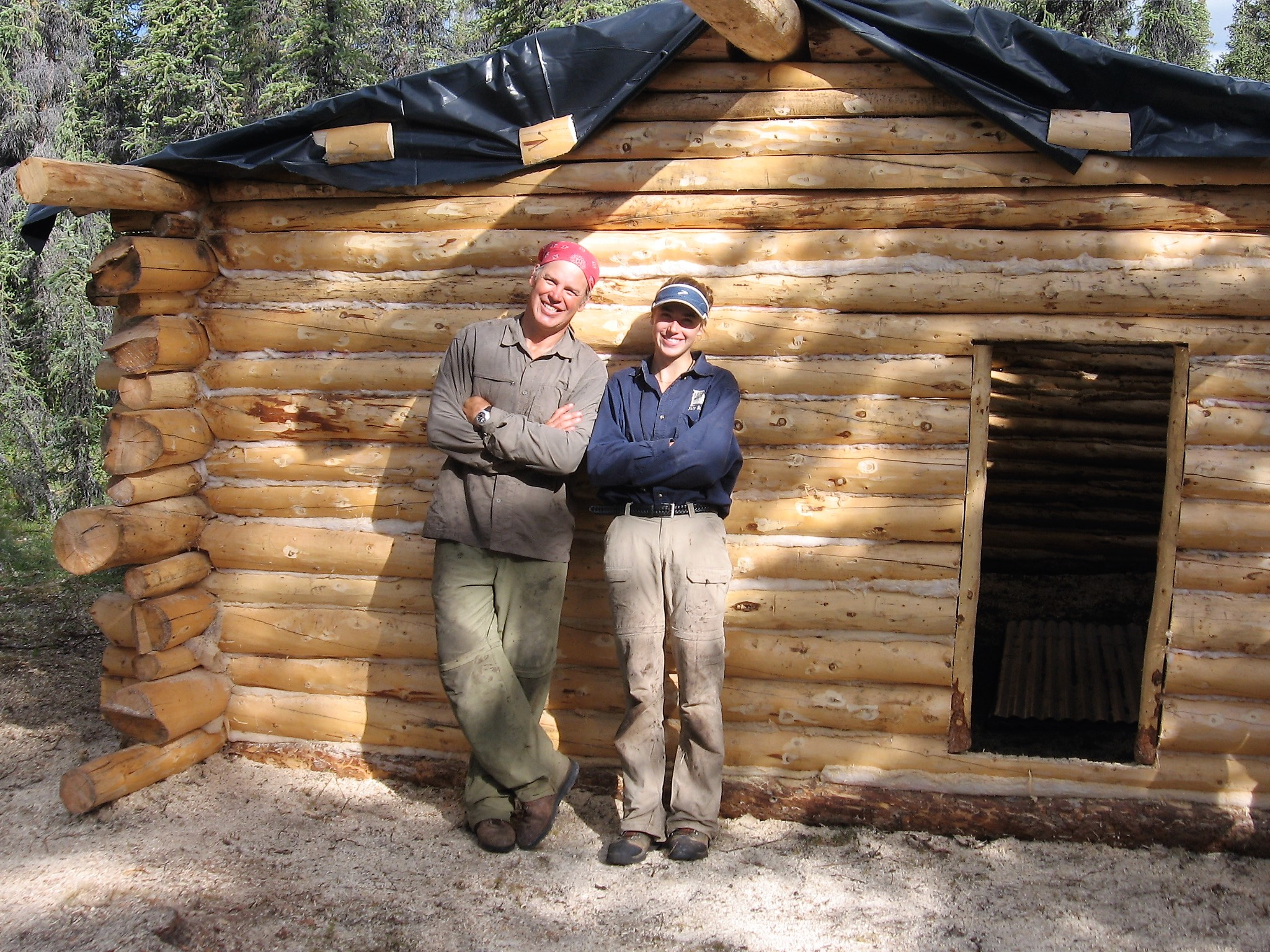 Aidan and Jim proudly standing in front of the cabin they helped build.